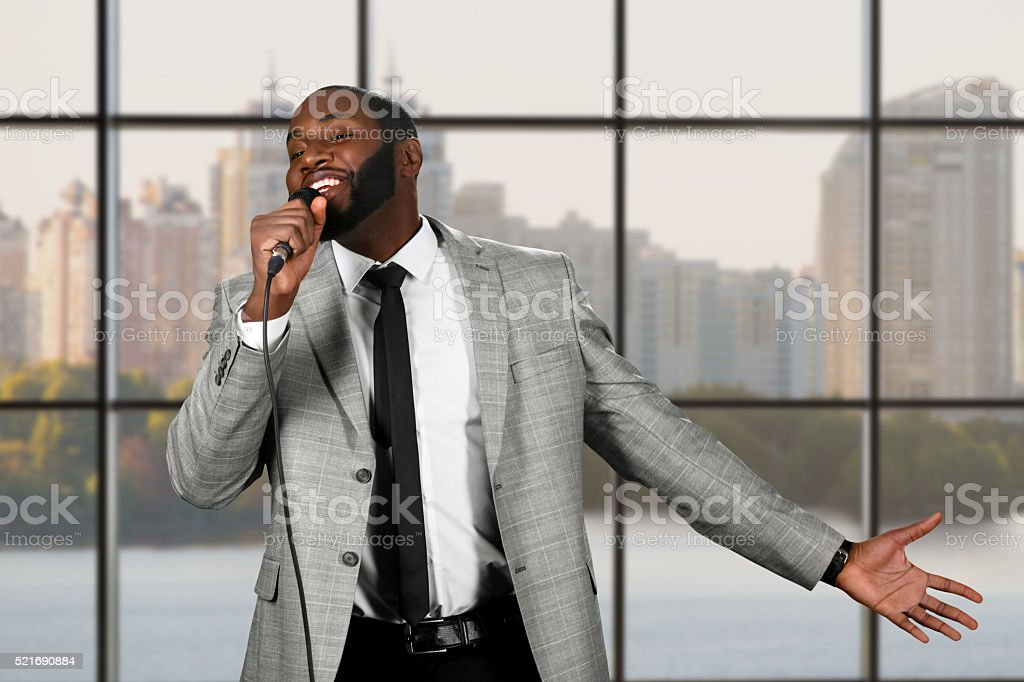 Black guy sings into microphone. stock photo