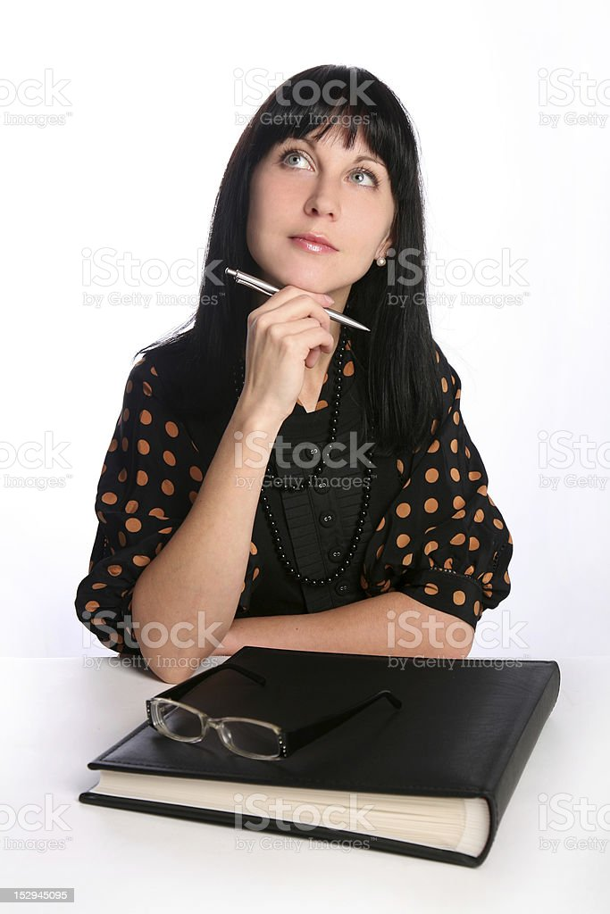 Black haired businesswoman sitting with album holding pen dreaming royalty-free stock photo