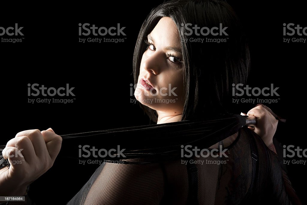 Black haired domme with flogger looking back over shoulder. stock photo