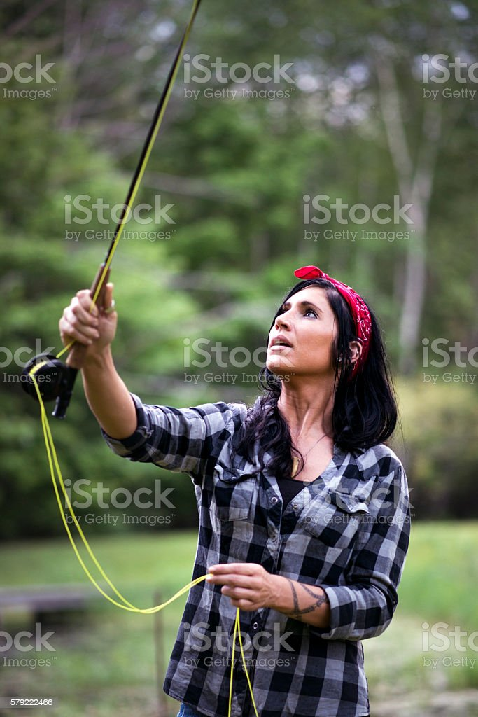 Black Haired Woman Casting a Fly Rod stock photo