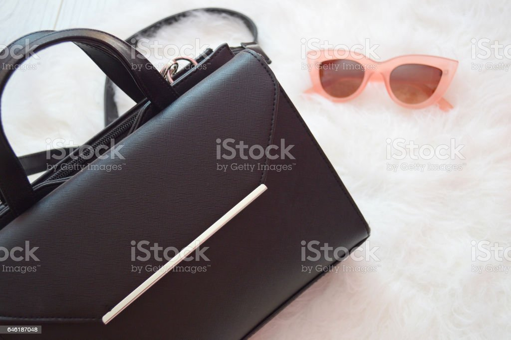 Black handbag and pink glasses on a white background. Fashion concept. top view stock photo
