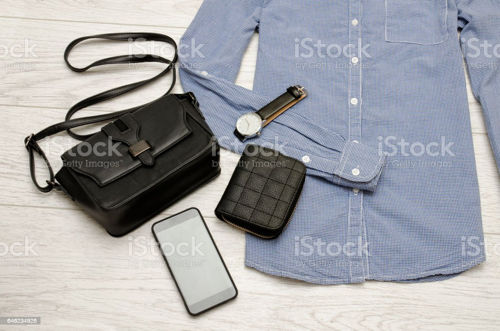 Black handbag, mobile phone, purse and a watch in the blue shirt. Fashion concept. top view stock photo