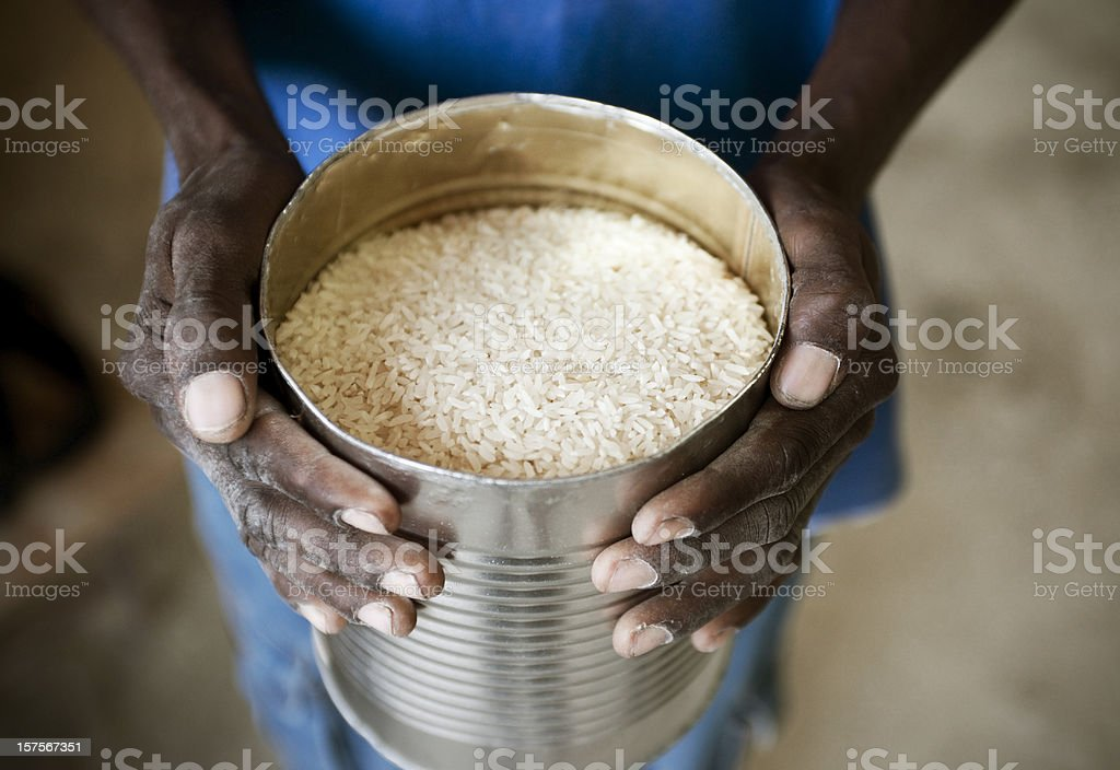 Black hands holding can of rice stock photo