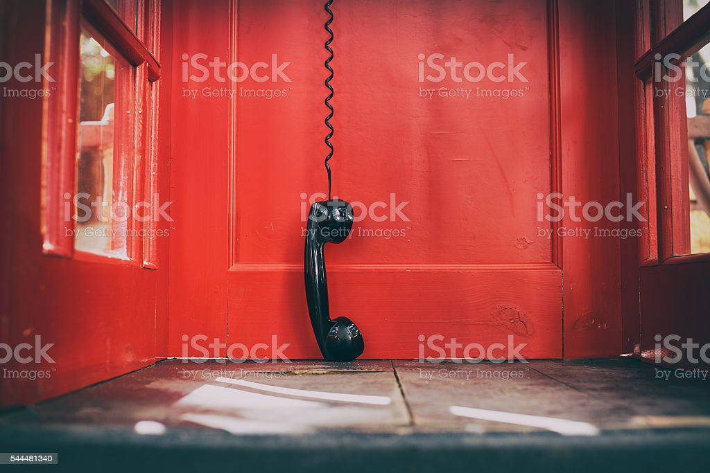black handset hanging in a red telephone box stock photo