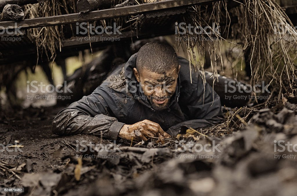 Black handsome young man climbing under obstacle during mud run stock photo