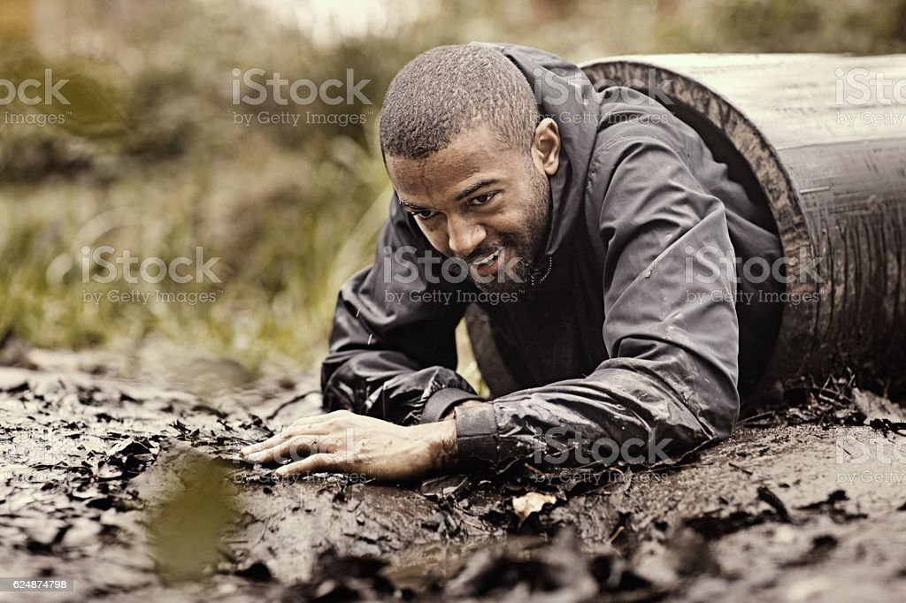 Black handsome young man crawling through obstacle during mud run stock photo