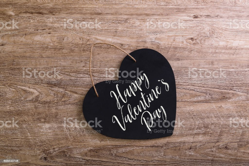 Black heart on wooden background. Love design. stock photo
