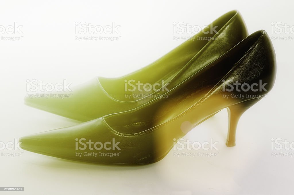Black high-heeled shoes caught in a sunbeam stock photo