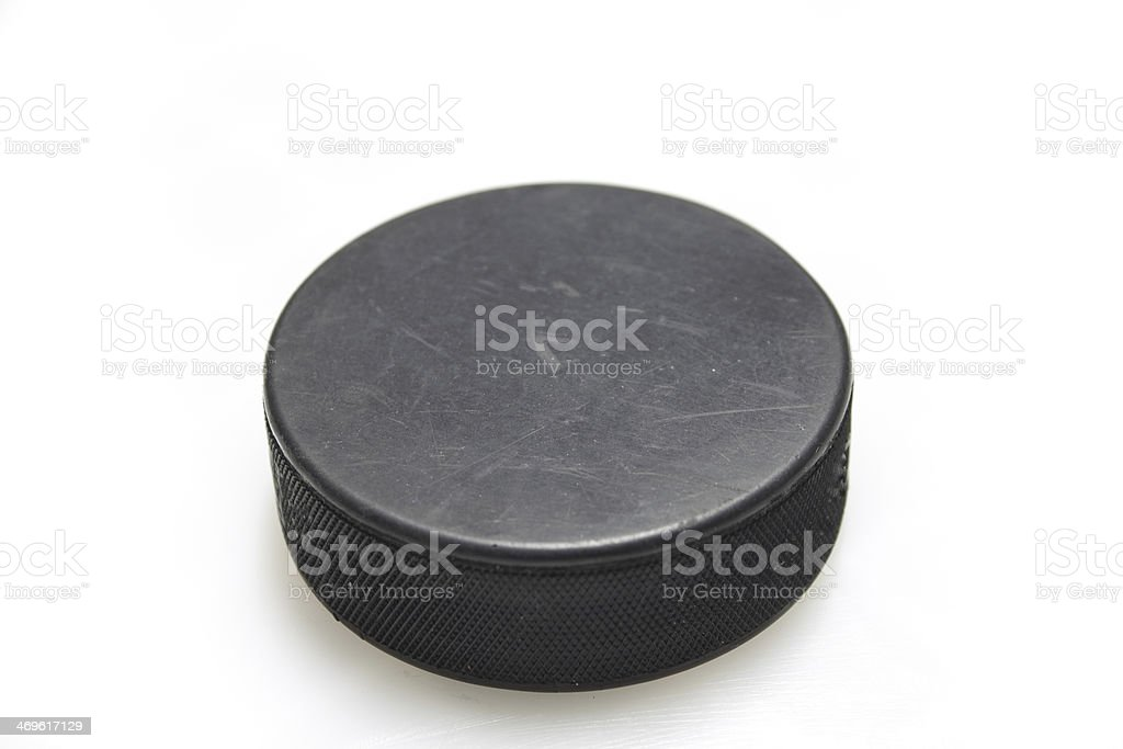 Black hockey puck in white background stock photo