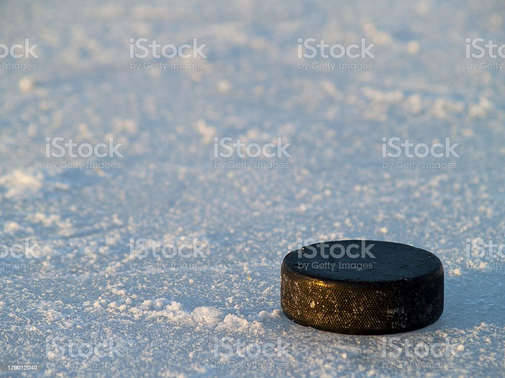 A black hockey puck on ice in the sunlight stock photo
