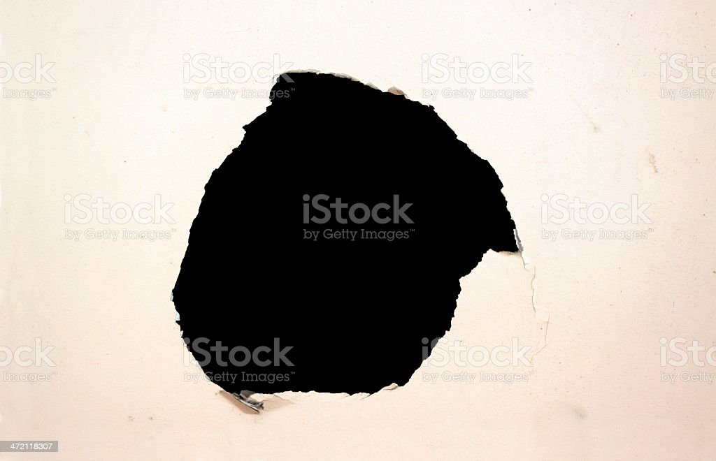 Black hole in old white damaged plaster wall, copy space stock photo