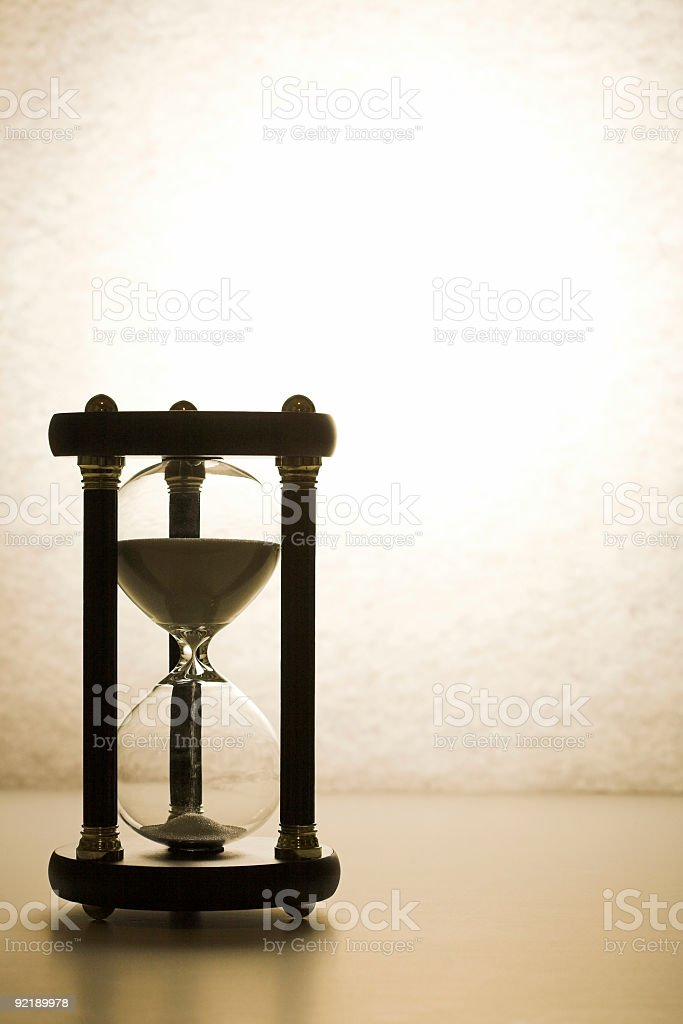 A black hourglass in a white room royalty-free stock photo