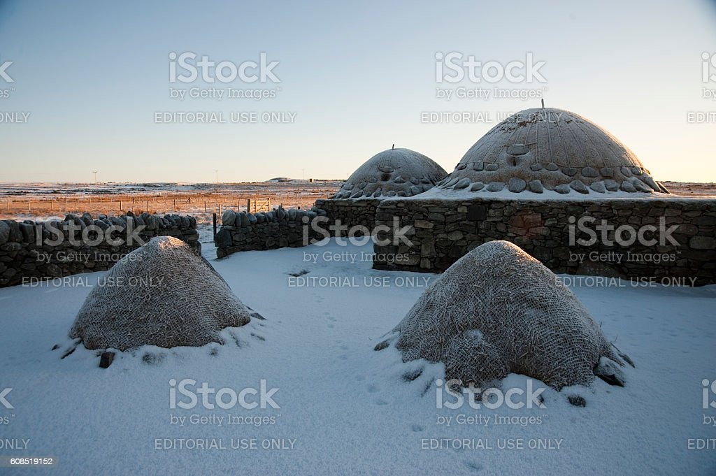'Black Houses' and peat stockpiles in the snow,Lewis,Scotland stock photo