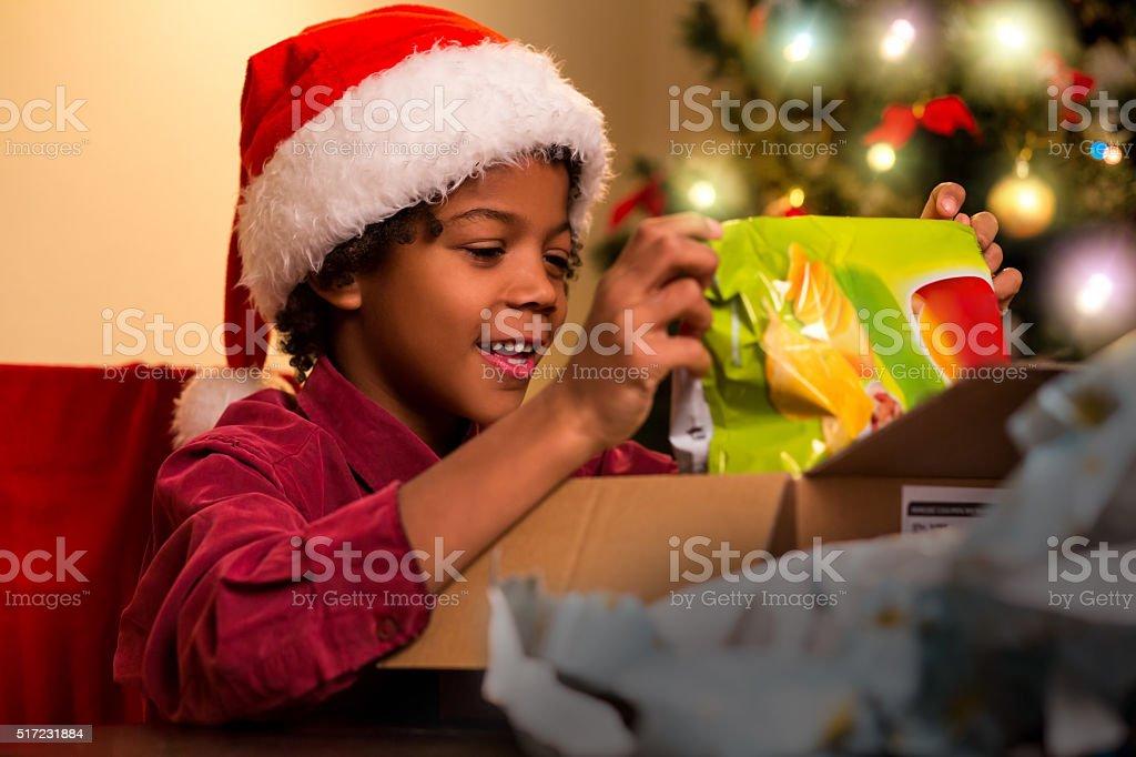 Black kid opening Christmas present. stock photo