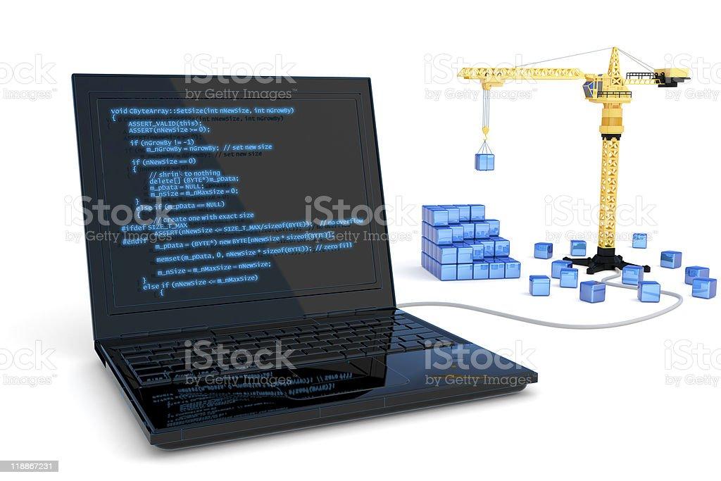 Black laptop controlling a mini crane lifting blue blocks stock photo