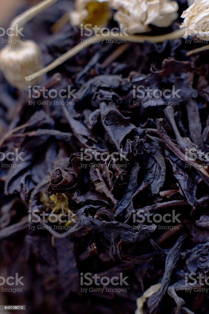 Black leaf tea with chamomile stock photo