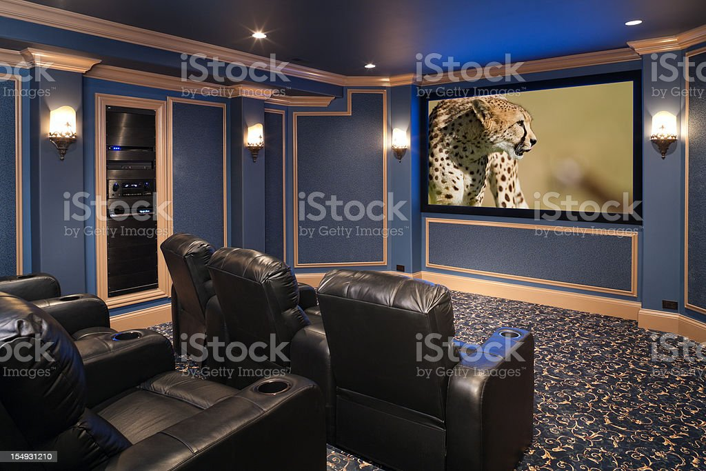 Black leather chairs adorn a beautiful home theatre. stock photo