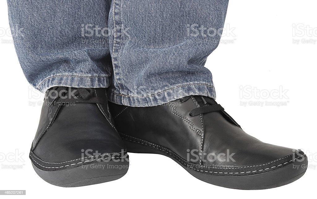 Black leather shoes, grey denim jeans, casual men's sneakers closeup stock photo
