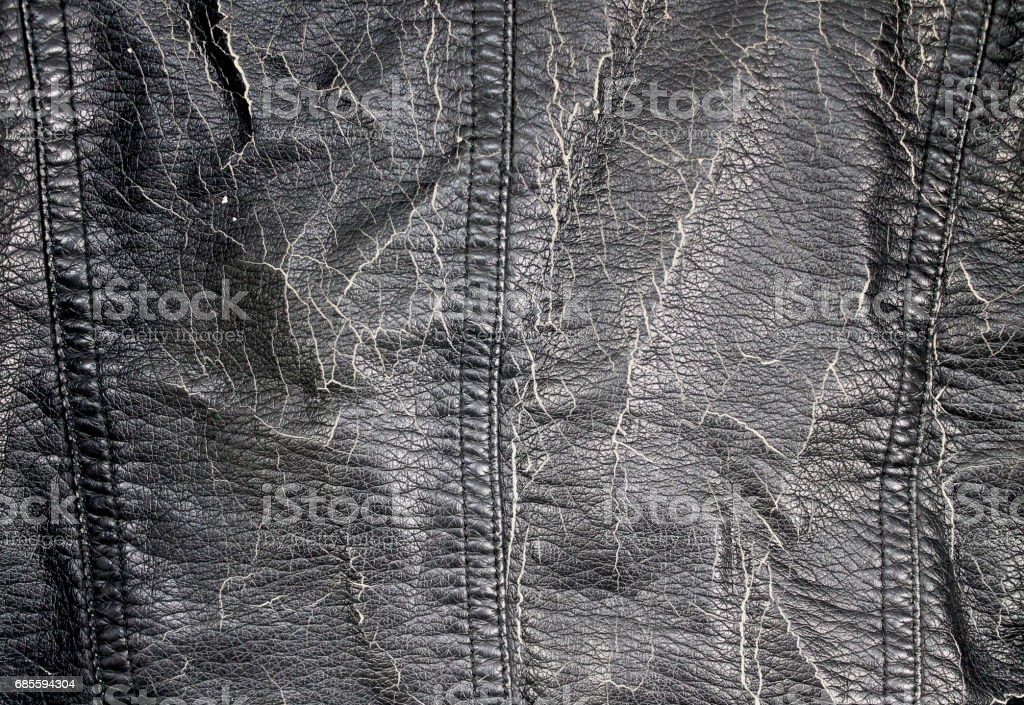Black leather texture background surface. A black dermantine texture close-up has passed many years of cracked skin. Vintage background of an old jacket stock photo