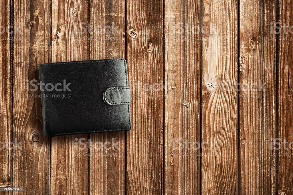 Black leather wallet on wooden table stock photo