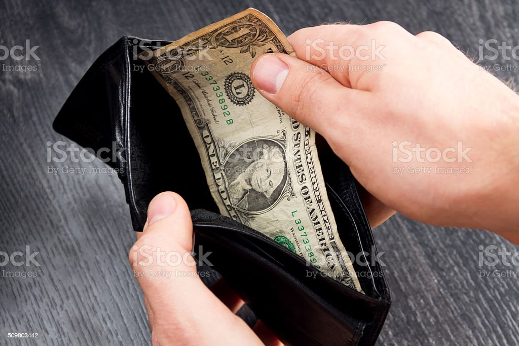 Black leather wallet with one dollar. Concept: poverty stock photo
