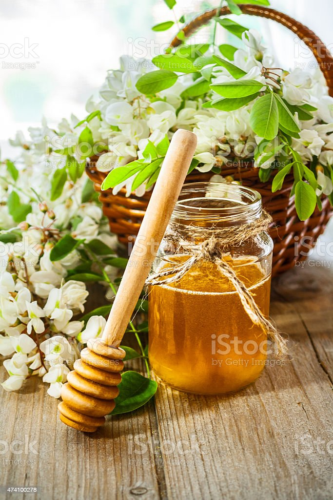Black locust flowers and Honey in jar stock photo