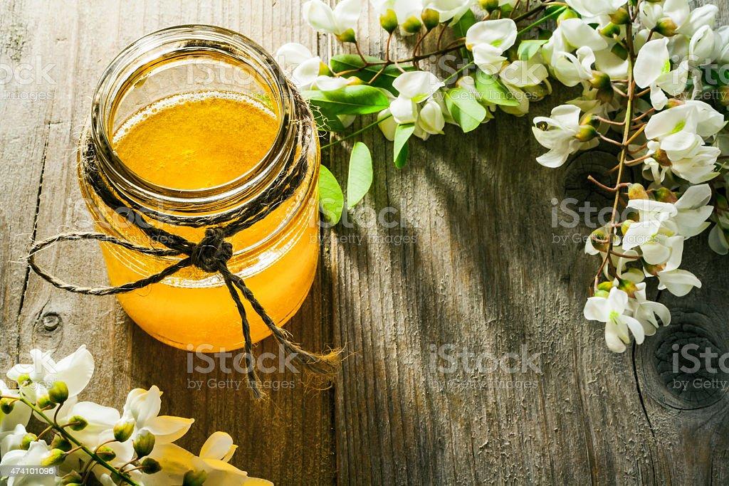 Black locust flowers and Honey in jar stock photo