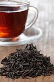 Black loose tea leaves with a cup of tea