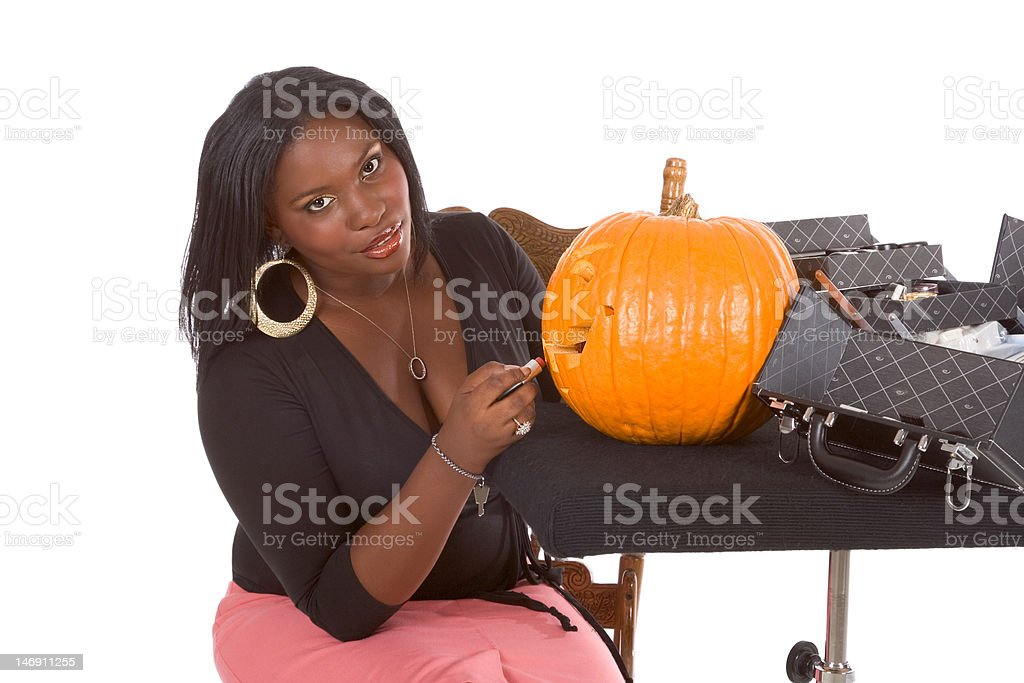 Black make-up artist decorating Halloween pumpkin royalty-free stock photo