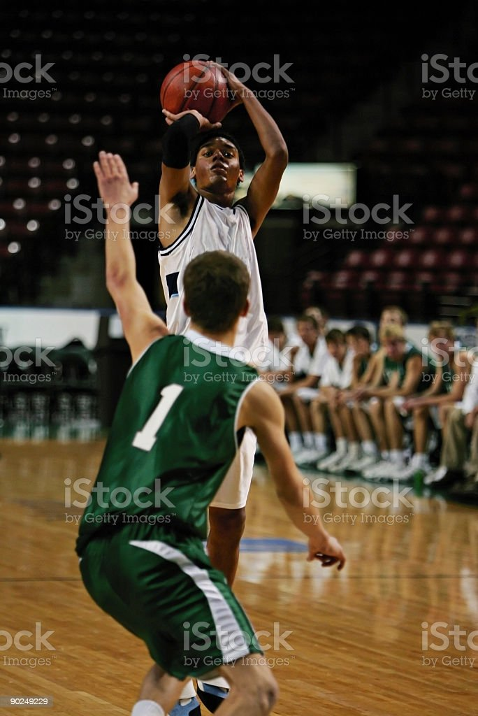 Black Male Basketball Player in White Gets Off Jump Shot royalty-free stock photo
