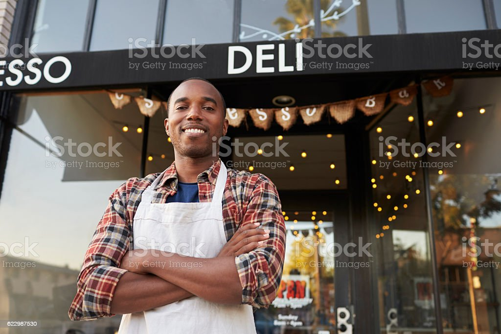 Black male business owner standing outside coffee shop stock photo