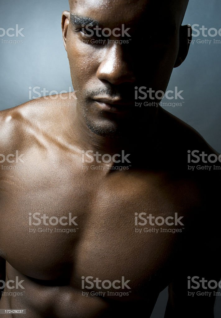Black Male Muscular Model In Dramatic Lighting Against Blue Background royalty-free stock photo