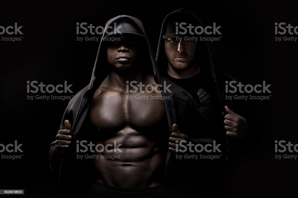 Black male posing in a hooded jacket with white male stock photo