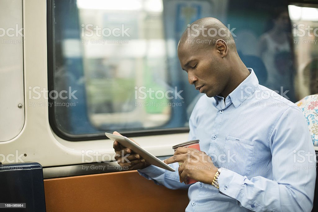 Black man commuting on subway with digital tablet stock photo