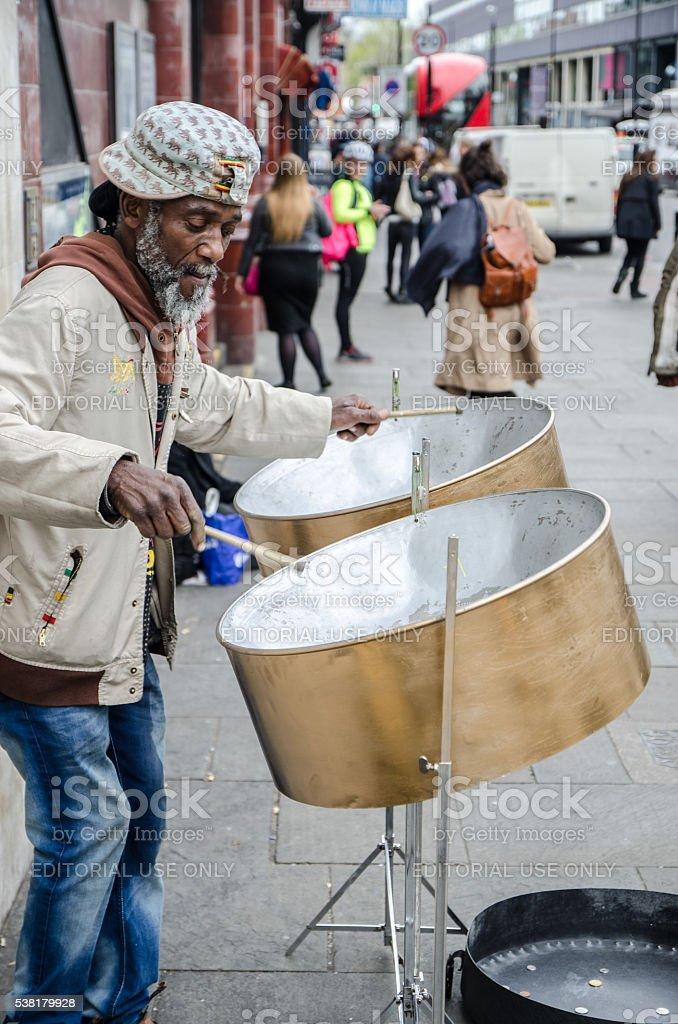 Black man playing Jamacan steel drum on street stock photo