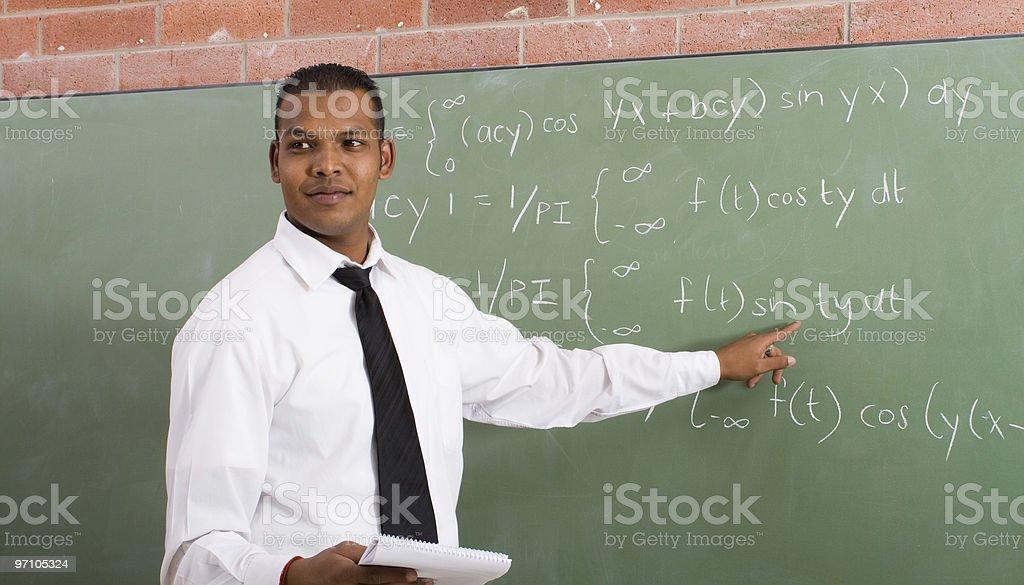 A black man teaching math at a chalkboard stock photo