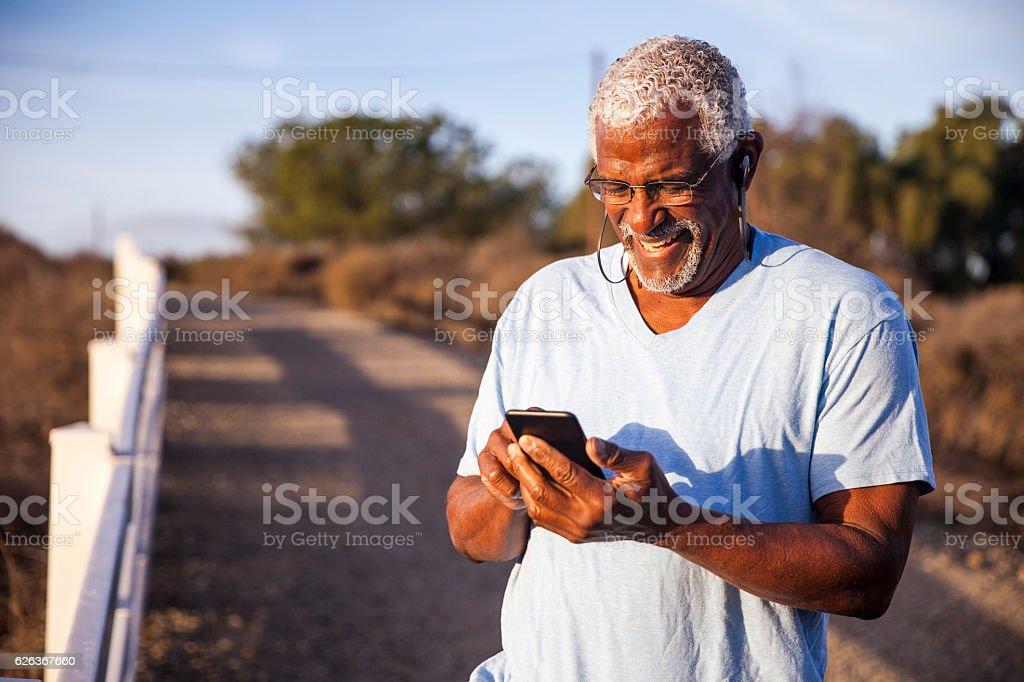 Black Man using smartphone on mountain trail stock photo