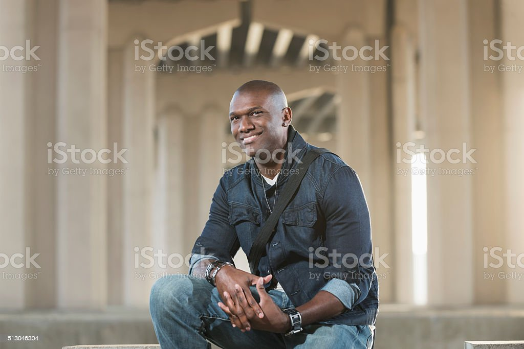 Black man with shaved head wearing jewelry and denim stock photo