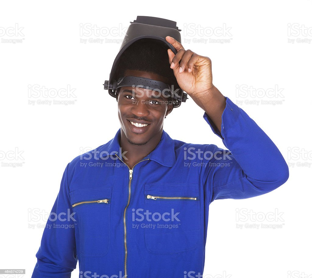 Black man working as a welder wearing a protective helmet stock photo