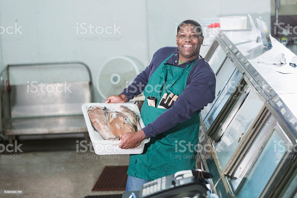 Black man working in a fish market stock photo