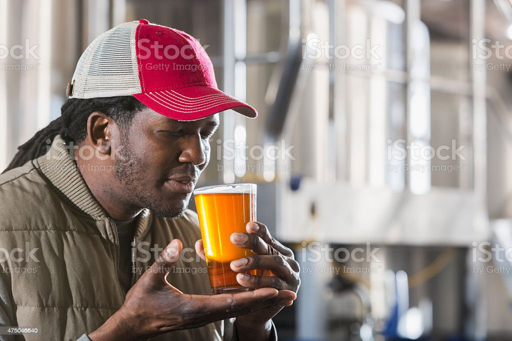 Black man working in a small brewery tasting beer stock photo