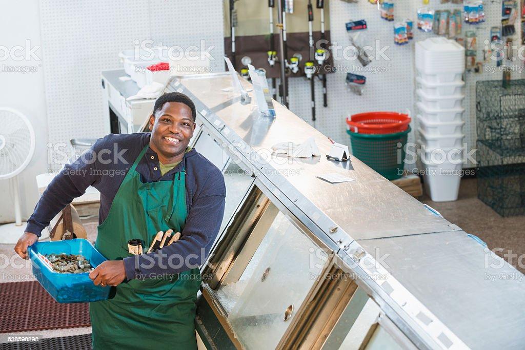 Black man working in fish market stock photo