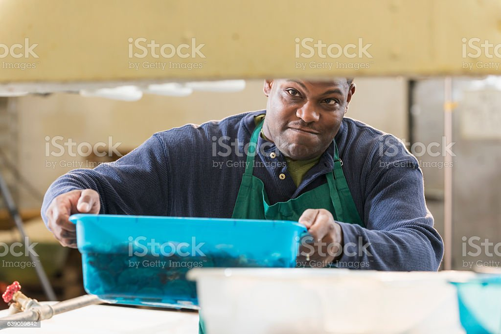 Black man working in seafood processing plant stock photo