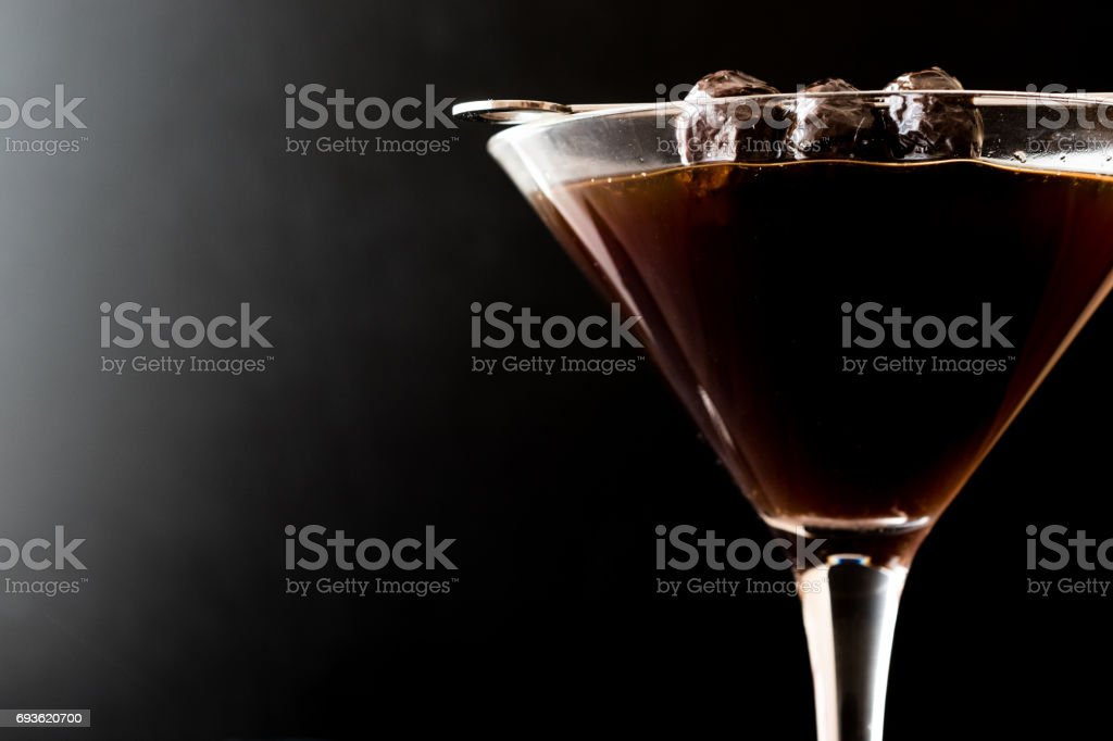 Black Manhattan Cocktail with olives on dark wooden surface. stock photo