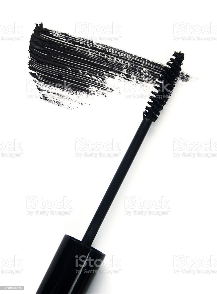 Black mascara brush and smear of mascara on white background stock photo