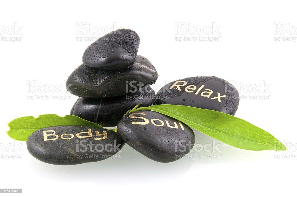 Noir pierres de massage avec feuilles vertes photo libre de droits