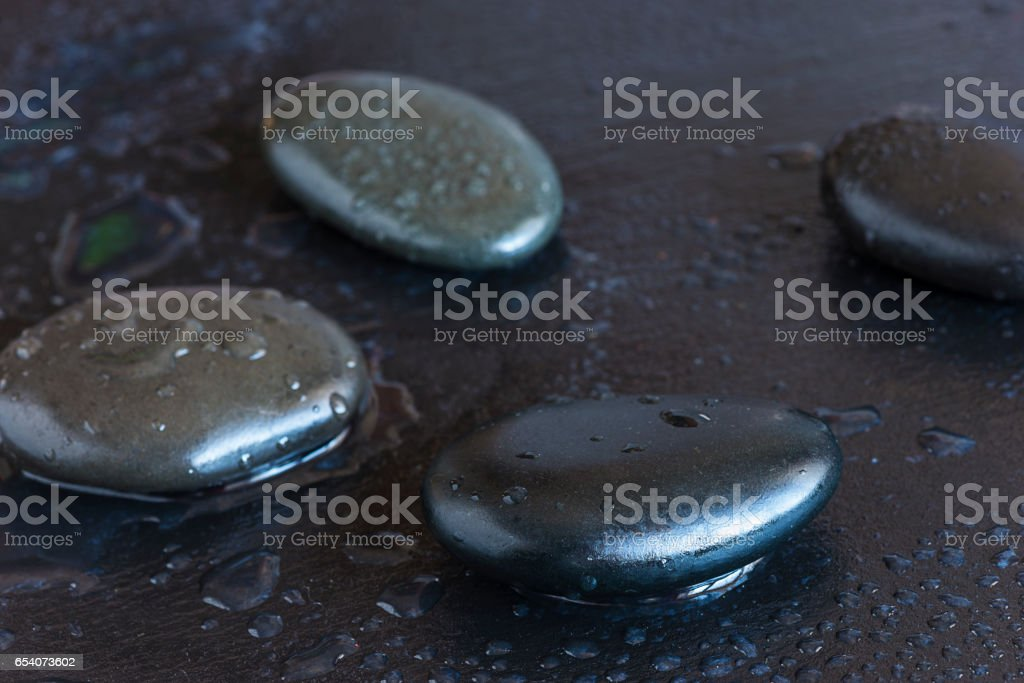 black massage stones with water drops stock photo