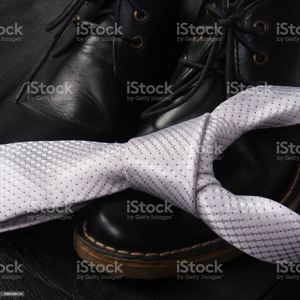 Black men's shoes and white tie stock photo