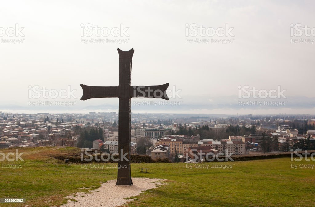 Black metal cross with Kutaisi city panorama stock photo