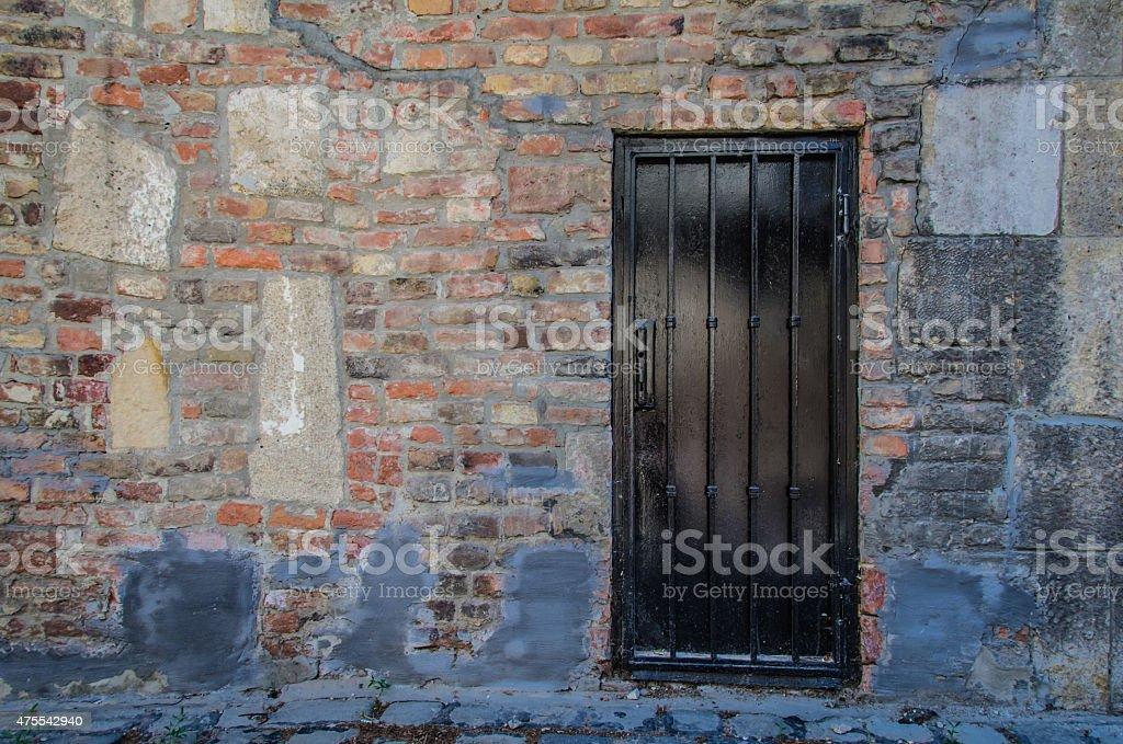 Black Metal Door and Brick Wall stock photo